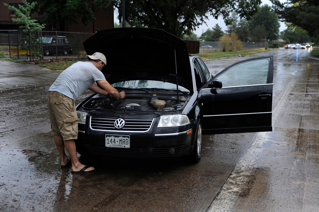 . DENVER, CO. - JULY 13:  Dean Vardal tried to dry out his engine after his Volkswagen stalled on Martin Luther King Boulevard after heavy rain fell over Denver Saturday evening, July 13, 2013.  Denver Police closed traffic in both directions as stalled cars were cleared from the parkway. Photo By Karl Gehring/The Denver Post