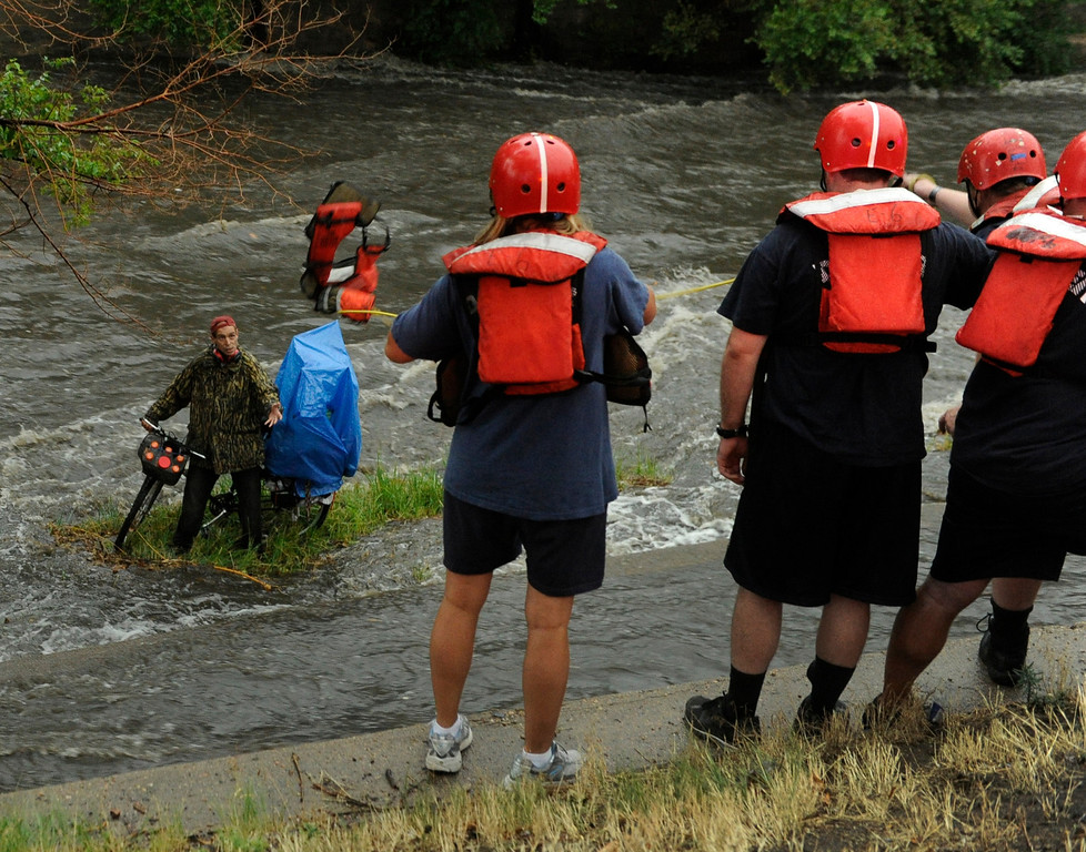 . DENVER, CO. - JULY 13:  Denver Firefighters threw a life jacket to homeless man Tom Pascarelli after rising water in Cherry Creek trapped him on an island near Broadway and Speer Saturday. Hard rains across the Denver metro area led to localized flooding Saturday evening, July 13, 2013.  Pascarelli said he had hoped to sleep under a bridge Saturday night. Photo By Karl Gehring/The Denver Post