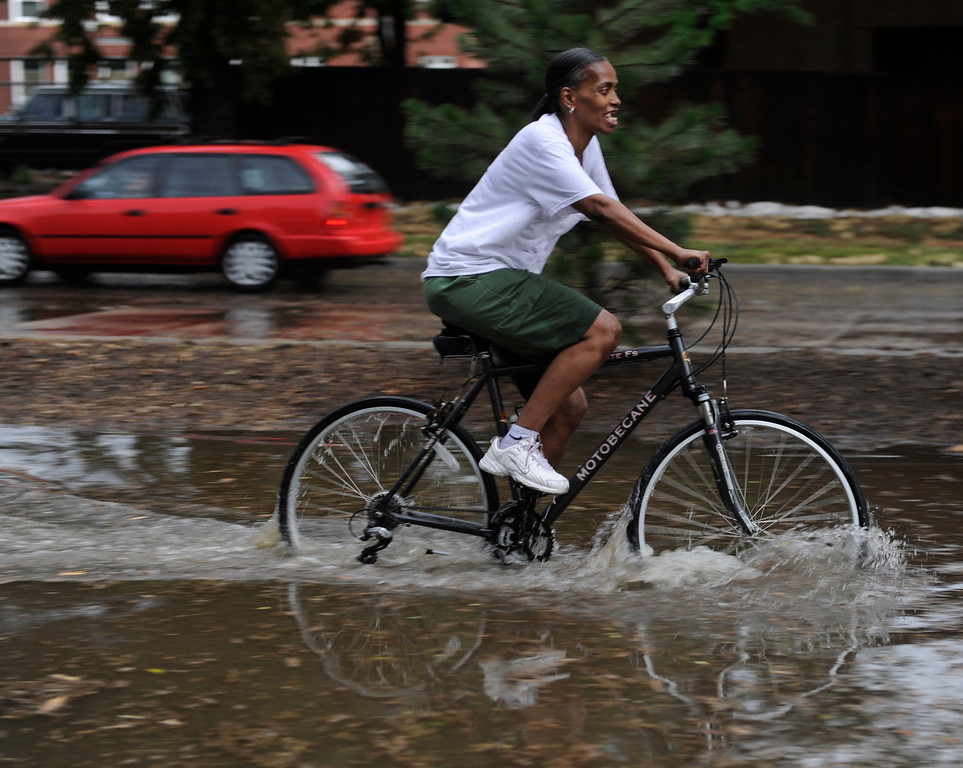 . DENVER, CO. - JULY 13:  A bicyclist made her way eastbound on a flooded stretch of Martin Luther King Boulevard after heavy tain fell over Denver Saturday evening, July 13, 2013.  Photo By Karl Gehring/The Denver Post