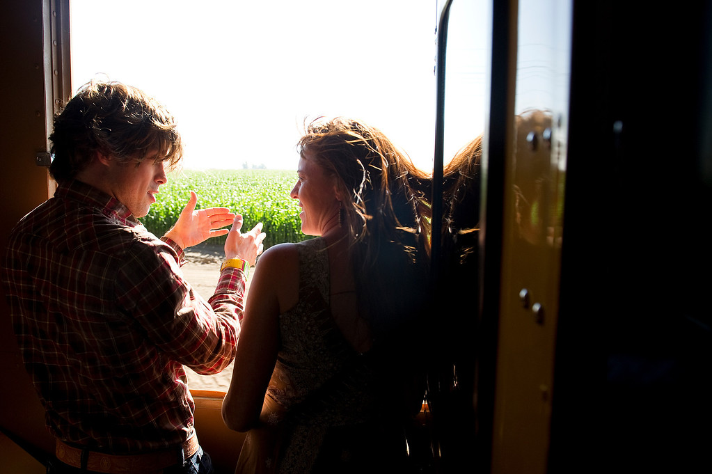 . GREELEY, CO - JULY 20: Andrew Rexroad, left, and Molly Kreck, right, talk and look out as the Denver Post Cheyenne Frontier Days train travels between Denver, Colorado, and Cheyenne, Wyoming, on July 20, 2013. (Photo by Daniel Petty/The Denver Post)