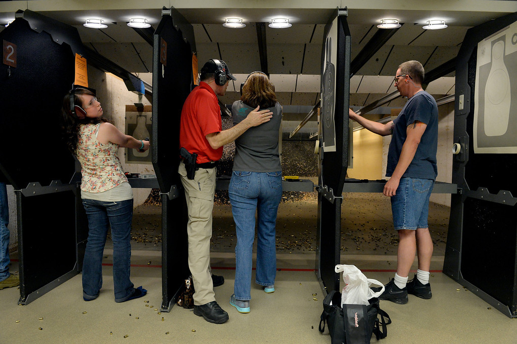 . CENTENNIAL, CO. - JULY 27: Range Safety Office, John Rickabaugh, center left, works with Christie Sterrett during a Multi-State Concealed Carry class at the Centennial Gun Club in Centennial, CO, July 27, 2013. The number of people seeking a concealed carry gun permit in Colorado has increased by 87 percent from last year. (Photo By Craig F. Walker / The Denver Post)