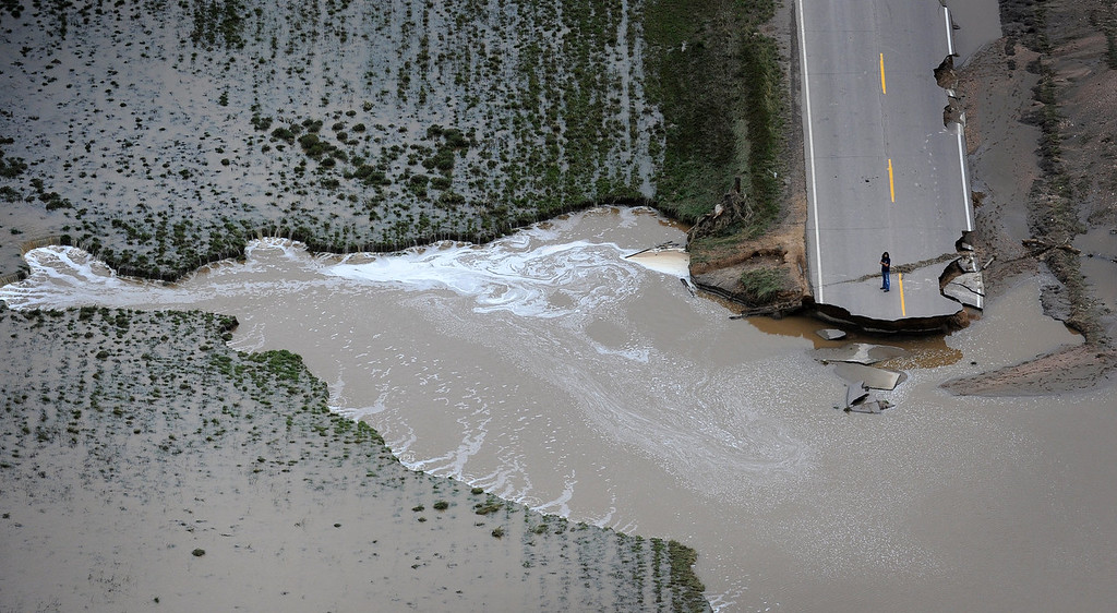 . A unidentified man stands on County Road 61 a looks at the damage cause when South Platte River washed out a major part of the road. Aerial photographs of the  South Platte River flooding cities and farms in Weld County Colorado. (Photo By Tim Rasmussen/The Denver Post)