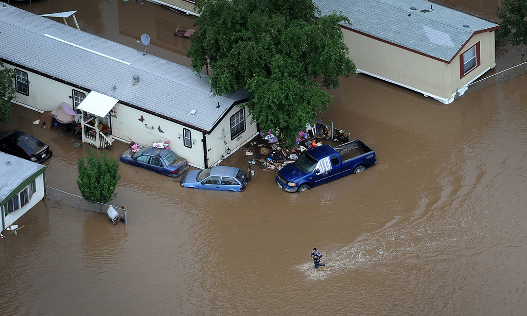 . People walk down 37th street in Evans Colorado, carrying belongings recovered from flooded  homes in the area. Aerial photographs of the Platte River flooding cities and farms in Weld County Colorado. (Photo By Tim Rasmussen/The Denver Post)
