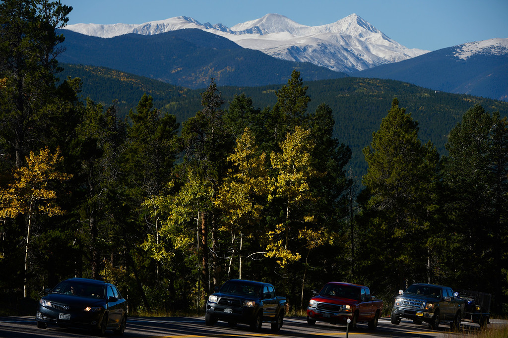 . NEDERLAND, CO - SEPTEMBER 28: A line of vehicles travel up highway 119 amongst aspen trees changing colors and a fresh blanket of snow between Central City and Nederland Colorado Saturday morning, September 28, 2103. (Photo By Andy Cross/The Denver Post)