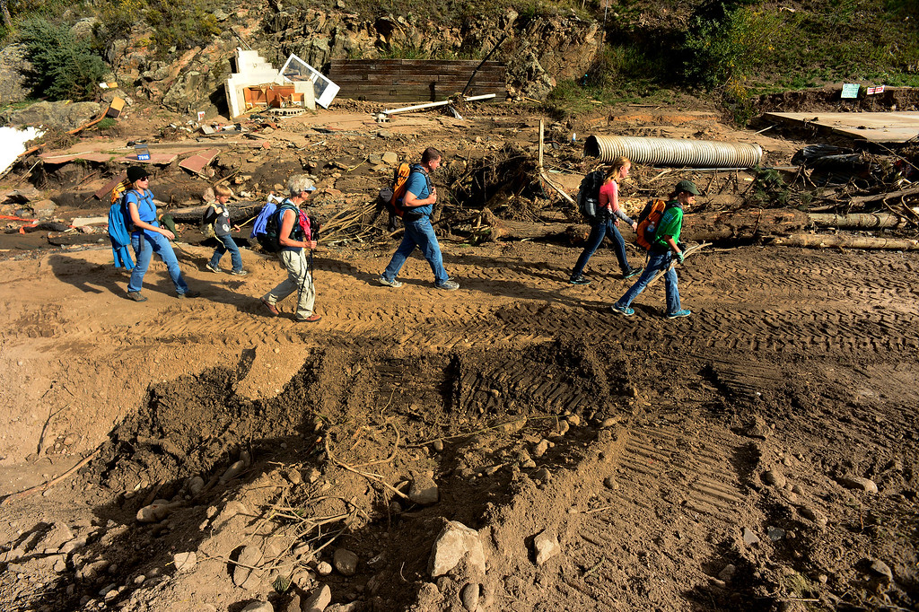 . GLEN HAVEN, CO - SEPTEMBER 30: Glen Haven resident Sonja McTeague, with walking sticks, walks with members of the Discher Family after they helped her clean her house in Glen Haven, Co on September 30, 2013.  (The family members from left to right are Carolyn, her son drew, 7, McTeague, Steve Discher and their daughters Lauren, 14, and Lexie, 11)  The Discher family came all the way from College Station, Texas just to help clean what they could in the town and help residents in any way they could.    (Photo By Helen H. Richardson/ The Denver Post)