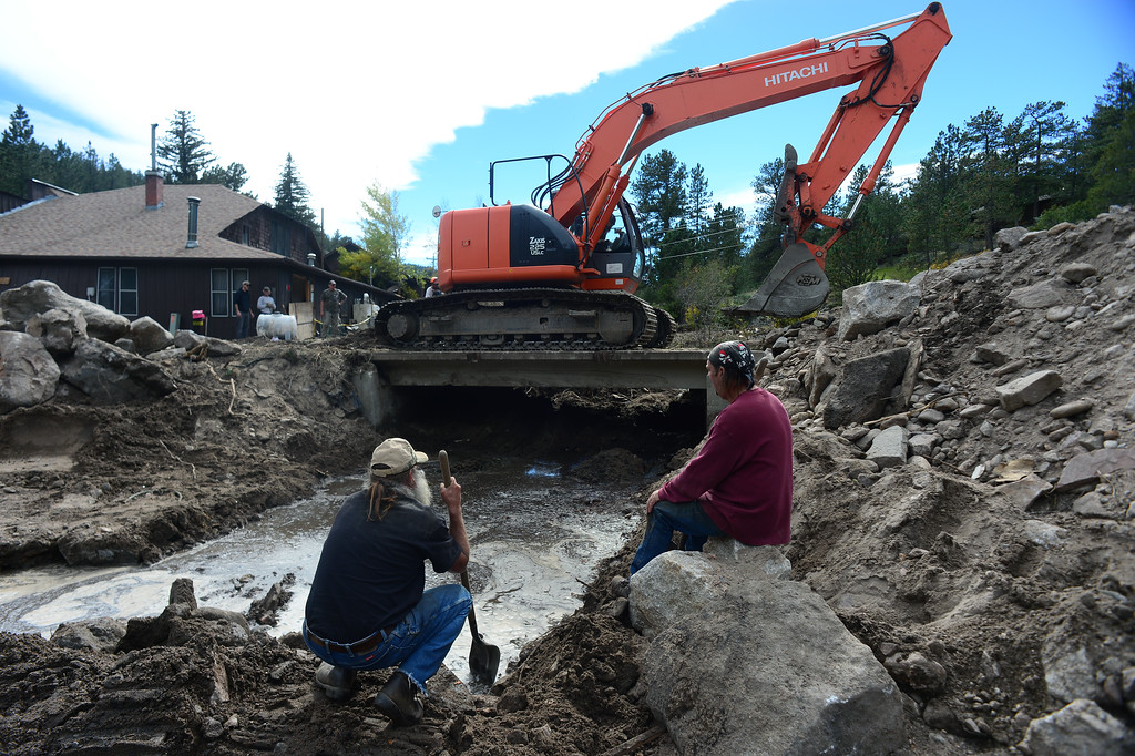 . GLEN HAVEN, CO - SEPTEMBER 30: Glen Haven residents Tim Sterkel, middle, and John Mills, right, watch as Travis Sterkel uses an excavator to test the strength of what is left of a bridge king over West Creek river and connecting on North Fork Road to Co. Rd 43 in Glen Haven, Co on September 30, 2013.  (Photo By Helen H. Richardson/ The Denver Post)