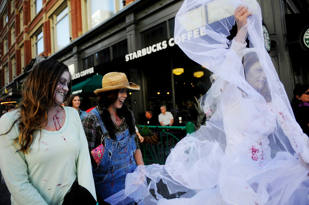 . Stacie Becker rips her zombie wedding dress as she heads down the16th Street Mall in Denver, CO on Oct. 19, 2013. Becker and her friends Crystal Warmack (far left) and Theresa Hinch were participating for their first time in the Zombie Crawl.  (Photo By Erin Hull/The Denver Post)