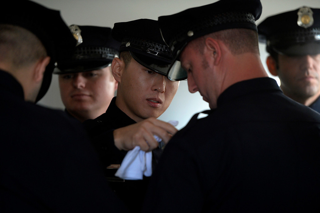 . DENVER, CO. - October 23: Denver Police Department recruit Alan Ma dresses the uniform of recruit Brian Kaiser before Class 13-1 take the stage  as the first graduates in five years at the Denver Police Academy. October 23, 2013 Denver, Colorado. (Photo By Joe Amon/The Denver Post)