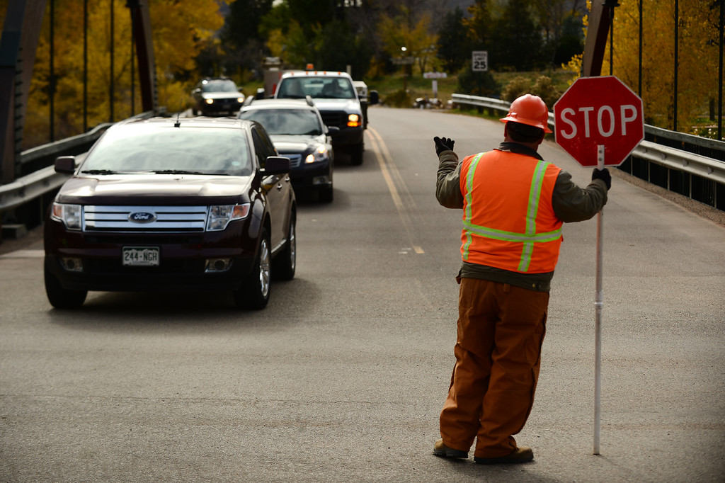. Flagger Mike Stueve waves the very first cars onto Highway 36 from Apple Valley road or CR 71 as the highway officially reopened near  Lyons, Co on November 4, 2013.  (Photo By Helen H. Richardson/ The Denver Post)