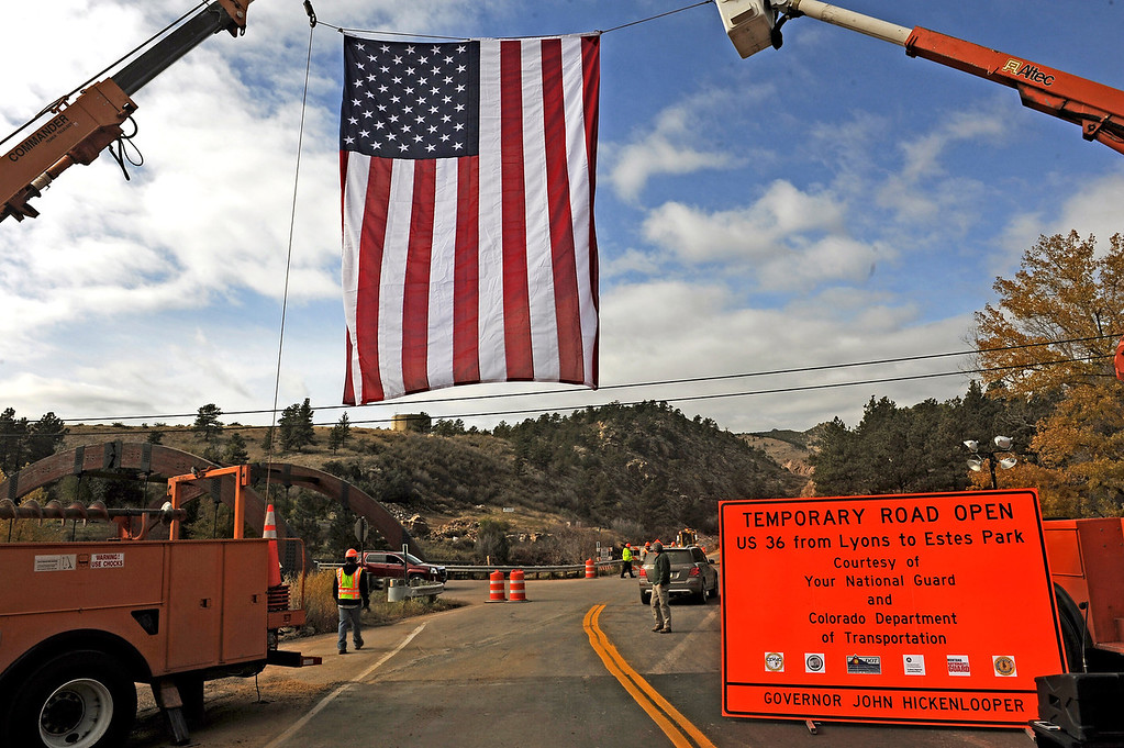. A giant American flag hangs over Highway 36 at the intersection of Co Road 71 prior to the opening of Highway 36  near  Lyons, Co on November 4, 2013.  The highway opened up 52 days after the massive flooding took out roads, bridges, and houses on September 12, 2013.  While it is called a  temporary road until all the work is complete, the  Highway 36 officially reopens giving access from Lyons to Pinewood Springs and to Estes Park.  (Photo By Helen H. Richardson/ The Denver Post)