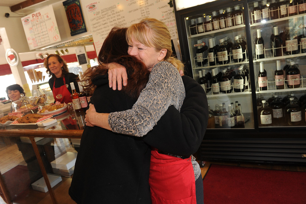 . Geri Plank, right, manager of   The Colorado Cherry Company gives a hug to highway flagger Isabell Florez in Pinewood Springs, Co on November 4, 2013.  The Colorado Cherry Company held a pie party for everyone in the community including highway workers and national guardsman to celebrate the reopening of Highway 36 through their community as  well as their first official day of reopening their restaurant.  Owners Kristi and Anthony Lehnert didn\'t charge a single person all day for any of the food that they ate.  (Photo By Helen H. Richardson/ The Denver Post)