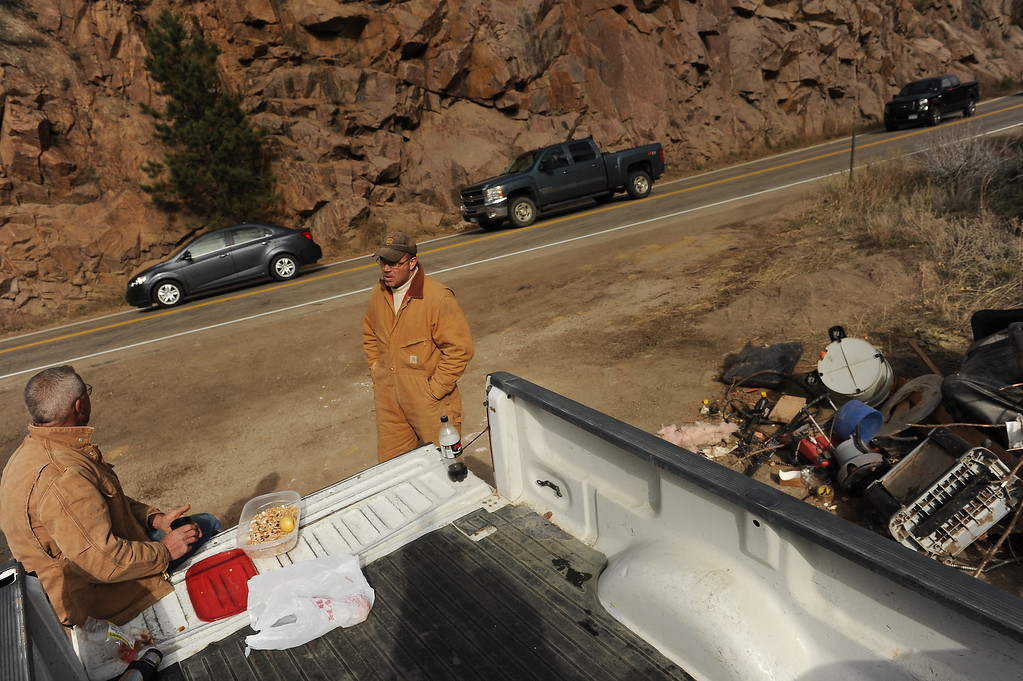 . Homeowner Rex Heiby, middle and his friend Lance Clymar, left, have lunch on the back of Heiby\'s truck while taking a break from working on his property up along Highway 36 near Lyons, Co on November 4, 2013 as cars are now able to use the highway.  Debris from his house lies on the side of the road.  (Photo By Helen H. Richardson/ The Denver Post)