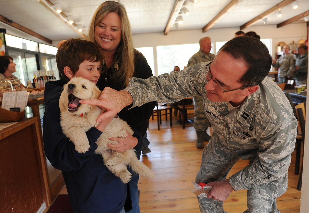 . Colorado National Guard Captain Darin Overstreet pets 5 weeks old Chinook as Wyatt Levy holds the cute puppy at  The Colorado Cherry Company in Pinewood Springs, Co on November 4, 2013.  (Wyatt\'s mother Laura Levy looks on.) The Colorado Cherry Company held a pie party for everyone in the community including highway workers and national guardsman to celebrate the reopening of Highway 36 through their community as  well as their first official day of reopening their restaurant.  Owners Kristi and Anthony Lehnert didn\'t charge a single person all day for any of the food that they ate.  (Photo By Helen H. Richardson/ The Denver Post)