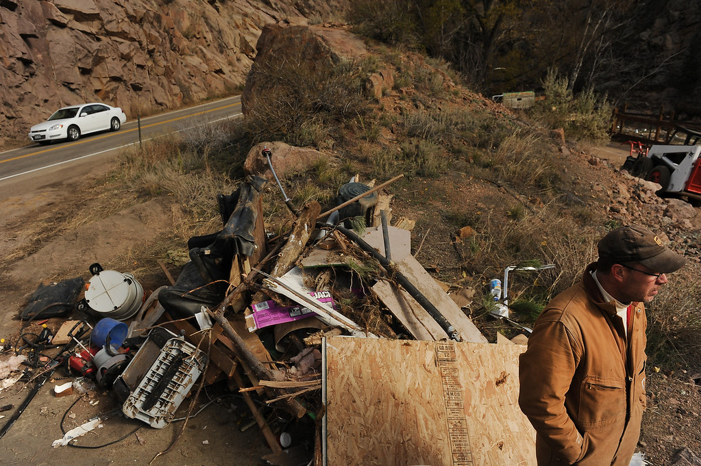 . Homeowner Rex Heiby, right, takes a break from working on his property up along Highway 36 near Lyons, Co on November 4, 2013 as cars now are able to drive to Estes Park.   Debris from his house lies on the side of the road.  (Photo By Helen H. Richardson/ The Denver Post)