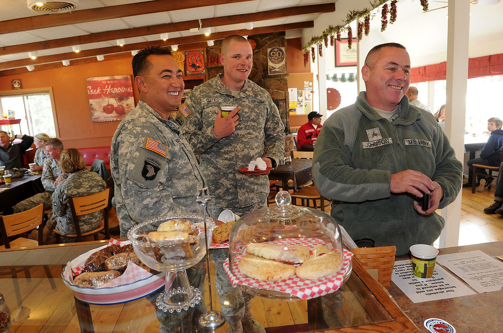 . Members of the Colorado National Guard from Buckley Air Force base try to pay for their food after enjoying cherry pie and other delicacies at The Colorado Cherry Company in Pinewood Springs, Co on November 4, 2013.  They are from right to left: Jay Johnson, Coe Gates and Samuel Vanzant. The Colorado Cherry Company held a pie party for everyone in the community including highway workers and national guardsman to celebrate the reopening of Highway 36 through their community as  well as their first official day of reopening their restaurant.  Owners Kristi and Anthony Lehnert didn\'t charge a single person all day for any of the food that they ate.  (Photo By Helen H. Richardson/ The Denver Post)