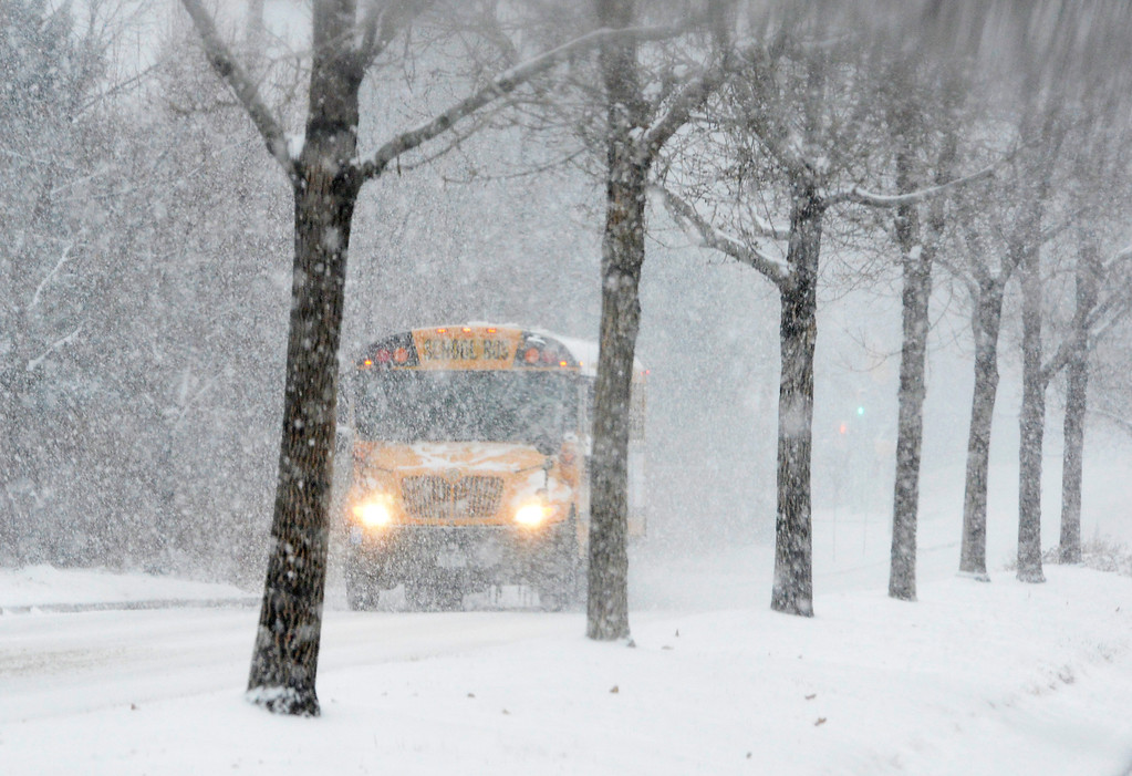 . A school bus makes his way along West Ken Caryl Avenue, November 21, 2013. Snow slows down morning rush hour in the metro area. (Photo by RJ Sangosti/The Denver Post)