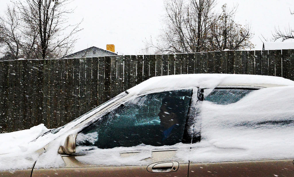 . A driver makes his way along West Ken Caryl Avenue, November 21, 2013. Snow slows down morning rush hour in the metro area. (Photo by RJ Sangosti/The Denver Post)