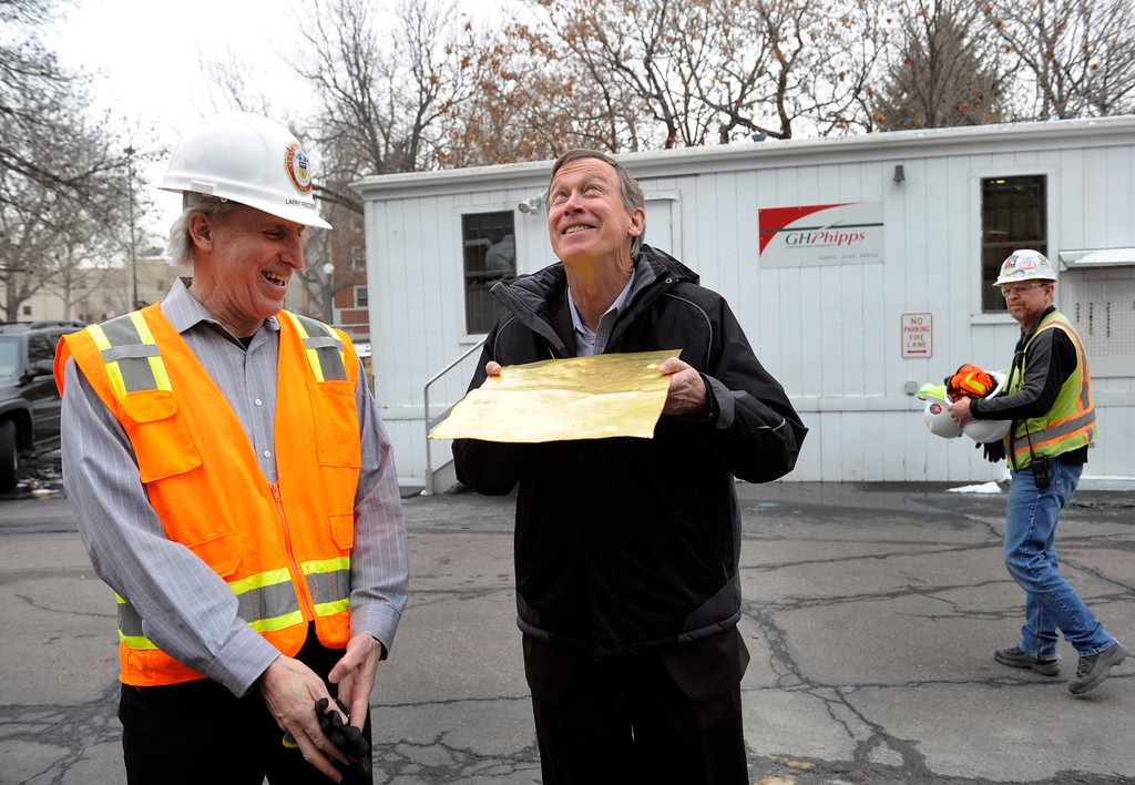 """. State Architect Larry Friedberg, left, gets a laugh as Governor John Hickenlooper pretends to sun himself with section of the 110 year-old gilded copper that was originally on the Capitol dome Friday, November 22, 2013. Progress continues on the restoration of the state Capitol dome, with crews reaching a milestone as they work hidden behind the large white scrim encircling the structure-brand new gold leaf is now being applied over the copper-clad dome. Crews are applying approximately 140,000, 3 1/8\"""" x 3 1/8\"""" gold leaves on top of the copper plates that cover the dome. The leaves are rolled out of 24-karat gold and contractors estimate it will take about 60 ounces of gold to cover the entire dome. (Photo by Kathryn Scott Osler/The Denver Post)"""