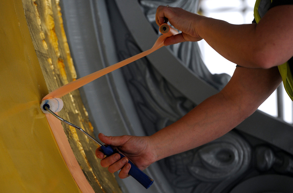 . Jill Eide, a gilder for Evergreene Architectural Arts, places the 24-karat gold leaf at the base of the dome Friday, November 22, 2013.  (Photo by Kathryn Scott Osler/The Denver Post)