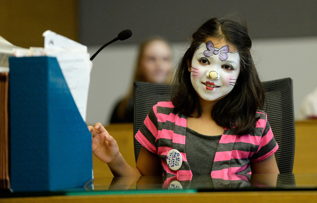 . Mariah Fernandez, 9, talks with judge Melanie Gilbert, November 22, 2013. Marieh and her two siblings are being adopted by their great uncle, Gilbert Fernandez, during the Denver Adoption Day event. (Photo by RJ Sangosti/The Denver Post)