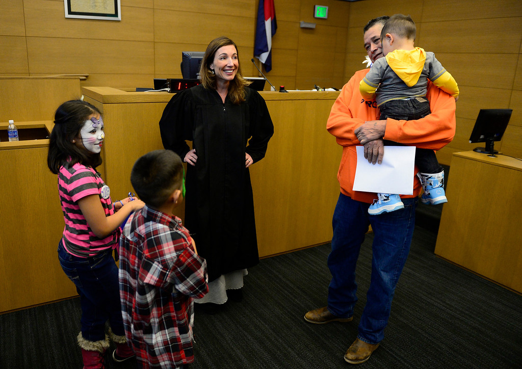 . Judge Melanie Gilbert talks with the Fernandez family after adoption court, November 22, 2013. The three siblings are being adopted by their great uncle, Gilbert Fernandez, during the Denver Adoption Day event. (Photo by RJ Sangosti/The Denver Post)