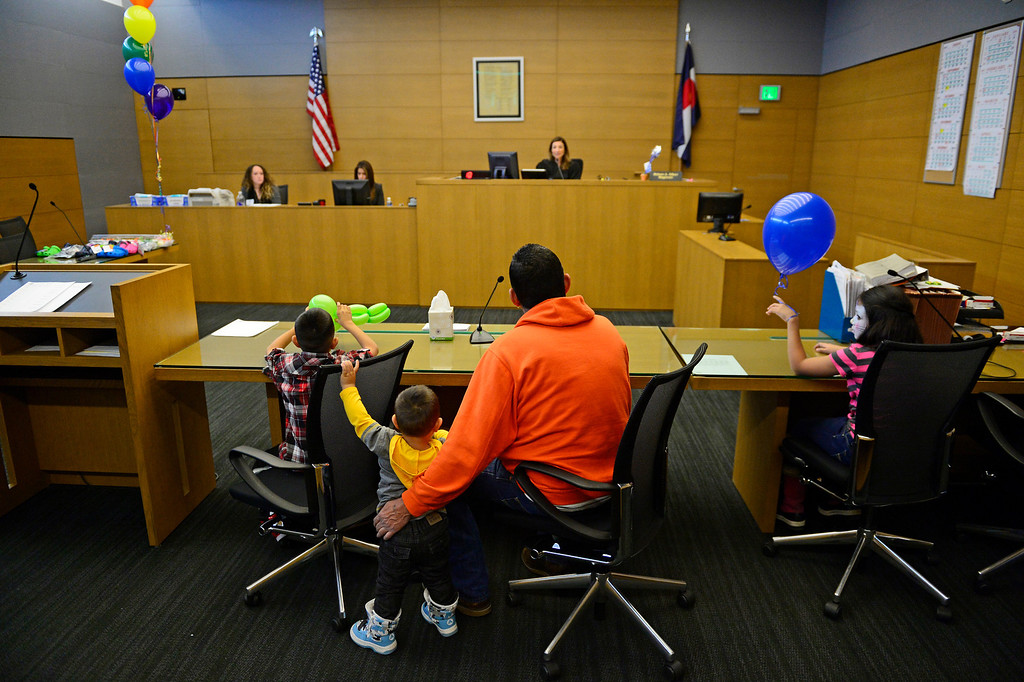 . Gilbert Fernandez,  center, with Giovannie, 7, left, Adam, 18 months, and Mariah, 9, talk with judge Melanie Gilbert, November 22, 2013. The three siblings are being adopted by their great uncle, Gilbert Fernandez, during the Denver Adoption Day event. (Photo by RJ Sangosti/The Denver Post)