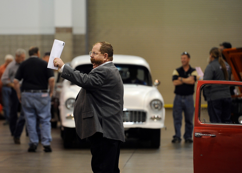 . Ringman Sammy Hamblin gathers bids during the car auction at the O\'Reilly Auto Parts Creme de la Chrome Rocky Mountain Auto Show takes place at the Colorado Convention Center downtown which runs through Sunday, Dec. 1, 2013. (Photo by Kathryn Scott Osler/The Denver Post)