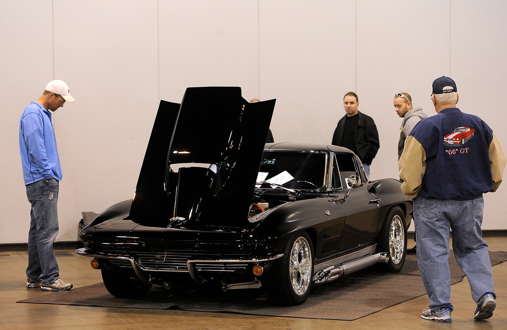 . A small crowd checks out a 1963 Corvette during the O\'Reilly Auto Parts Creme de la Chrome Rocky Mountain Auto Show takes place at the Colorado Convention Center downtown which runs through Sunday, Dec. 1, 2013. (Photo by Kathryn Scott Osler/The Denver Post)