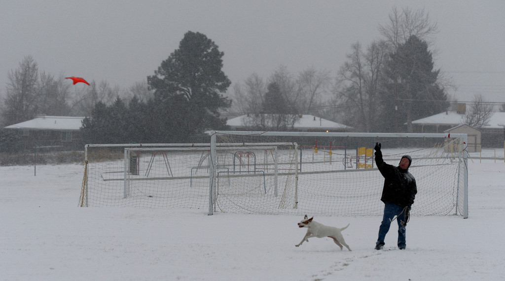 . Mike Mehrens exercises his dog, Grace, in a field off West Euclid Ave in Littleton, CO December 04, 2013. Low temps in Denver expected to hit minus 6 on Wednesday and minus 9 Thursday, according to the weather service forecast. Snow could pile up 7 to 11 inches along the Front Range. (Photo By Craig F. Walker / The Denver Post)