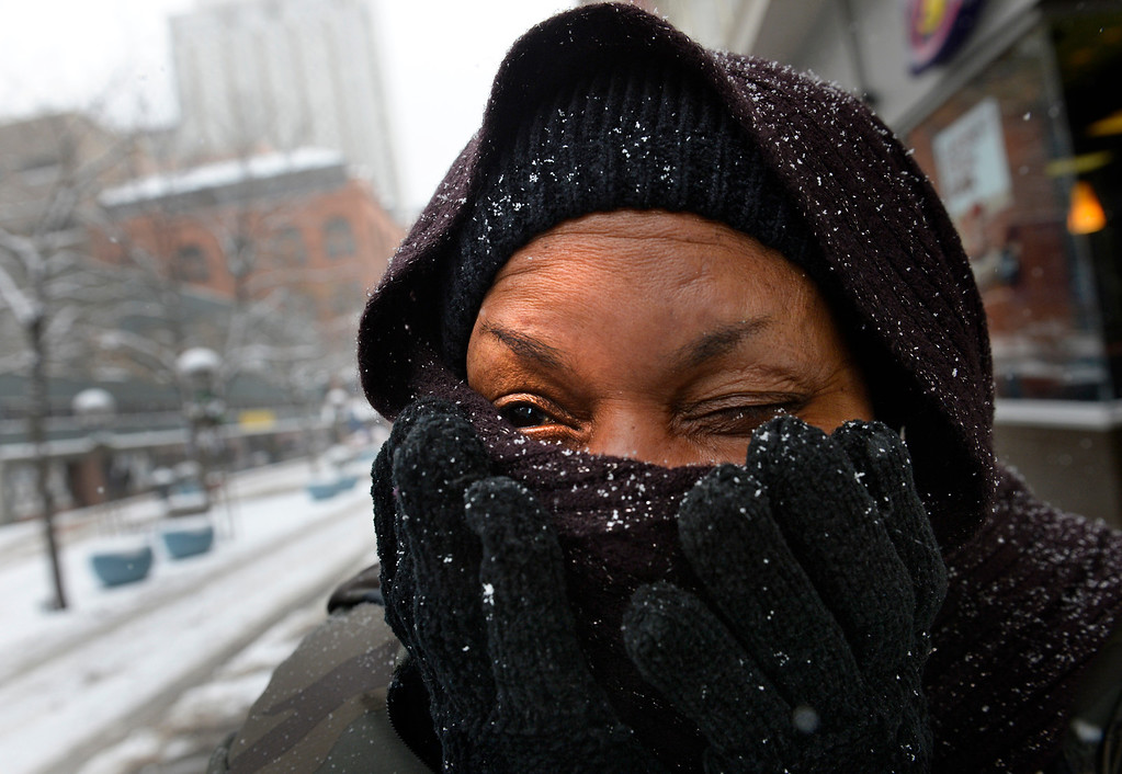 . Mary Harts tries to keep warm as she walks downtown Denver, December 04, 2013. A larger winter storm has moved into much of Colorado bringing freezing temperatures and snow. (Photo by RJ Sangosti/The Denver Post)