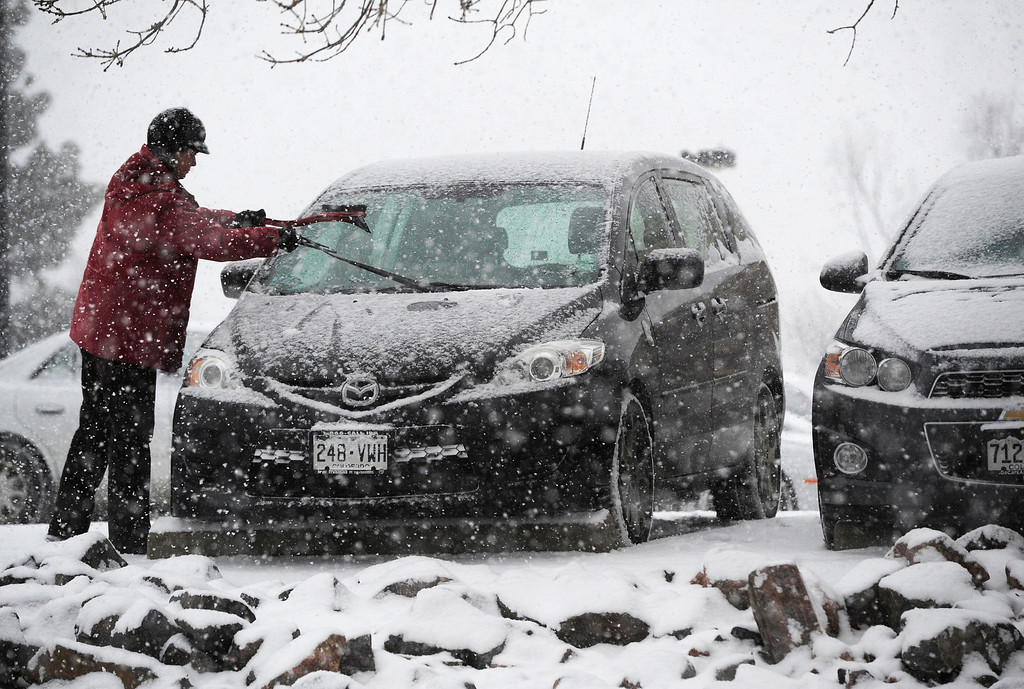 . A woman clears her windshield from snow in a parking lot near Colfax Ave and Colorado Blvd Wednesday morning, December 04, 2013. (Photo By Andy Cross/The Denver Post)