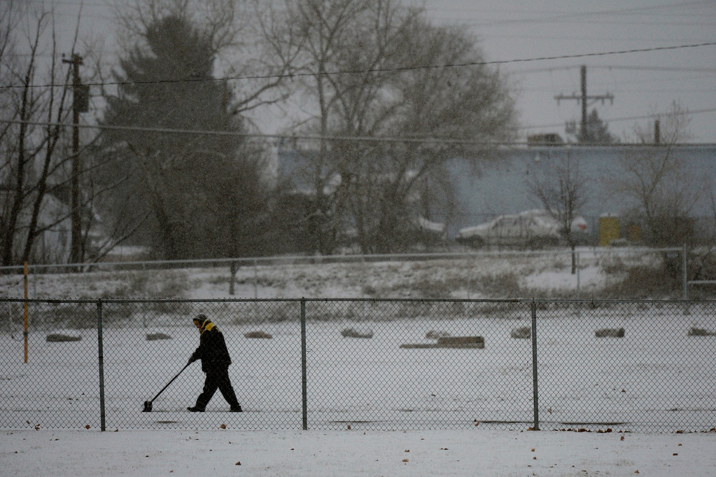 . A man shovels the sidewalk on South Acoma Street in Littleton, CO December 04, 2013. Low temps in Denver expected to hit minus 6 on Wednesday and minus 9 Thursday, according to the weather service forecast. Snow could pile up 7 to 11 inches along the Front Range. (Photo By Craig F. Walker / The Denver Post)