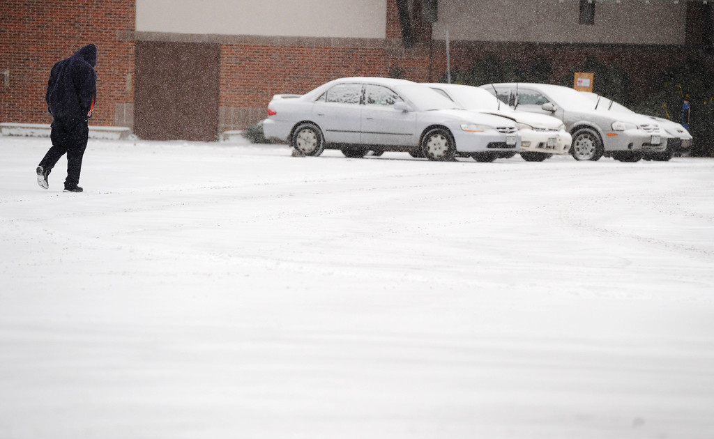 . DENVER, CO - DECEMBER 04:  A man walks through light snow in a parking lot near Leetsdale and Monaco Pkwy Wednesday morning, December 04, 2013. (Photo By Andy Cross/The Denver Post)