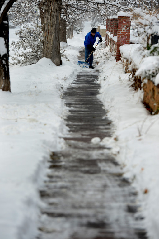 . Rick Hoover shovels his neighbor\'s sidewalk along Highland Ave in Boulder, Co on December 4, 2013.  Cold temperatures and snow gripped the metro area and frigid temperatures are expected to linger through the weekend. (Photo By Helen H. Richardson/ The Denver Post)