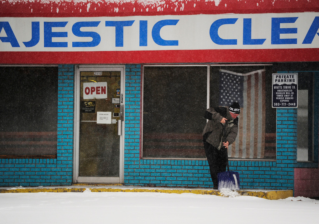 . A man clears snow from a sidewalk in front of the Majestic Cleaners near Evans Ave and Monaco Pkwy Wednesday morning, December 04, 2013. (Photo By Andy Cross/The Denver Post)