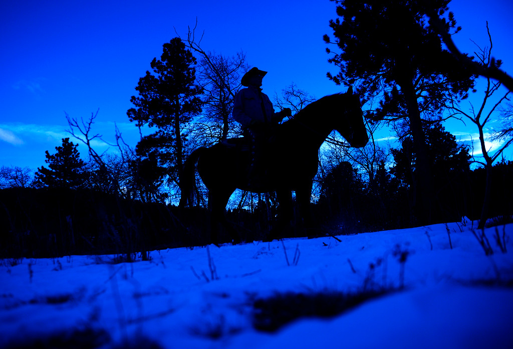. Tom Jones, a wrangler at Sundance Trail Guest Ranch near Red Feather Lakes, takes an evening ride, December 20 2013.  The ranch allows guests to ride year-round. (Photo by RJ Sangosti/The Denver Post)