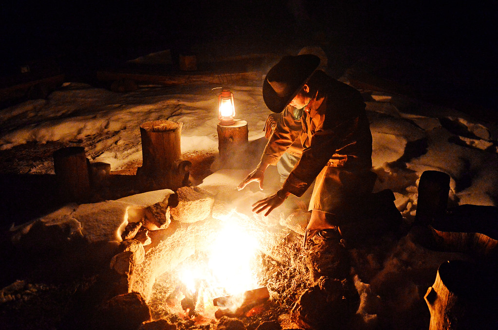 . Dan Morin, owner of Sundance Trail Guest Ranch near Red Feather Lakes, warms his hands by the fire, December 20 2013. The ranch, about an hour west of Fort Collins, allows guests to ride horses year-round. (Photo by RJ Sangosti/The Denver Post)