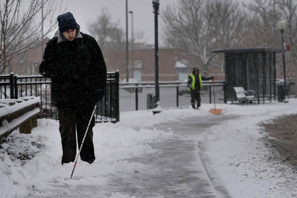 . Paul Sandoval uses his white cane to navigate the path on his way to work at Beyond Sight in Littleton, CO January 04, 2014. Temperatures will linger in the low 20s Saturday as a storm drops anywhere from 3 to 5 inches of snow in the Denver metro area, forecasters say.(Photo By Craig F. Walker / The Denver Post)