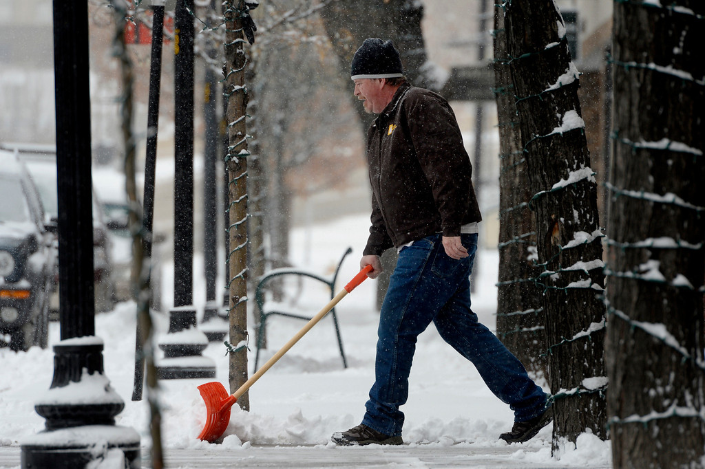 . Manager Mike Dodge shovels snow outside the Main Street Apartments in downtown Littleton, CO January 04, 2014. Temperatures will linger in the low 20s Saturday as a storm drops anywhere from 3 to 5 inches of snow in the Denver metro area, forecasters say.(Photo By Craig F. Walker / The Denver Post)