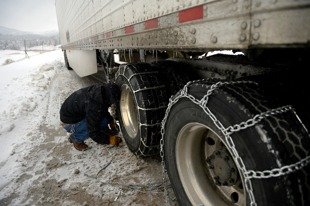 . Mike Anderson of Missouri switching out his traction cables for chains as ice and snow stopped him from climbing Hwy 285 near Settlers Road on his way to Center Co April 03, 2014 Conifer, CO (Photo By Joe Amon/The Denver Post)