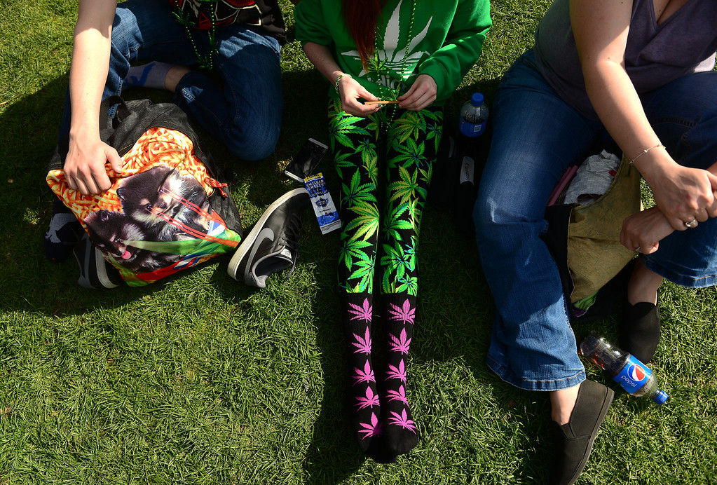 . A woman rolls a joint while wearing marijuana plant inspired socks and leggings while attending the Colorado 420 Rally at Civic Center Park in Denver on April 20, 2014.  Thousands of people lit up marijuana pipes, cigarettes, joints, and bongs at exactly 4:20 pm to celebrate the now legal use of marijuana in the state of Colorado.  (Photo By Helen H. Richardson/ The Denver Post)
