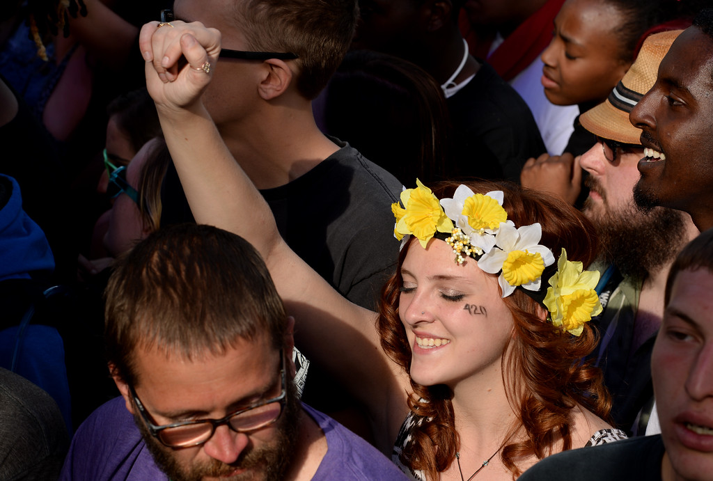 . A young girl with flowers on her head and the 420 symbol on her cheek enjoyed the rap music of B.o.B. who performed at the Colorado 420 Rally at Civic Center Park in Denver on April 20, 2014.  Thousands of people lit up marijuana pipes, cigarettes, joints, and bongs at exactly 4:20 pm to celebrate the now legal use of marijuana in the state of Colorado.  (Photo By Helen H. Richardson/ The Denver Post)