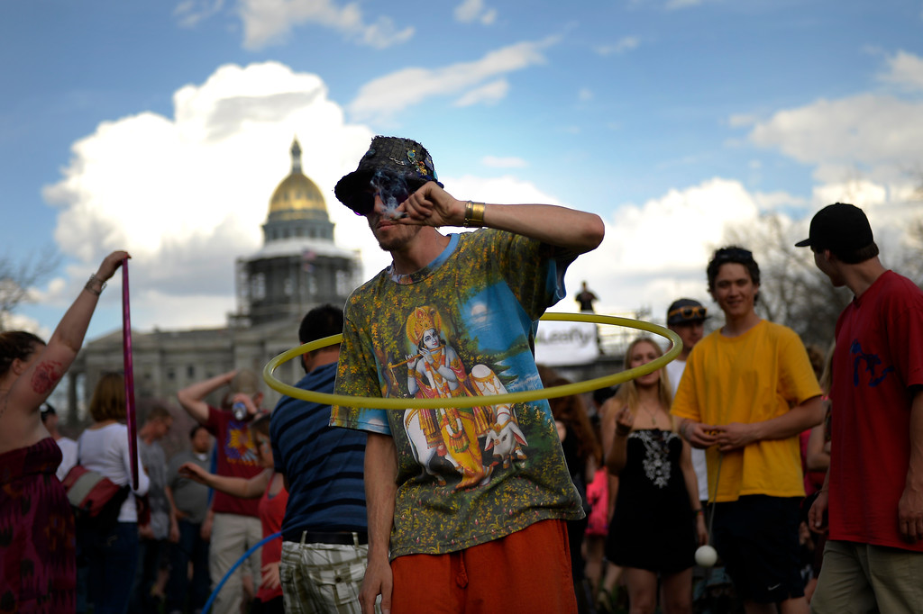 . 22 year old Don Blosser of Denver smokes a joint as he hula hoops after the smoke out at the 420 celebration at the Denver 420 Rally in Civic Center Park April 20, 2014 Denver, CO (Photo By Joe Amon/The Denver Post)