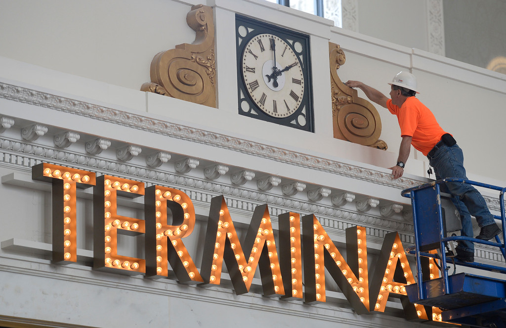 . Denver\'s Union Station will soon reopen. They showed off some of the renovated facility on Thursday, July 10, 2014. A worker in the Great Hall polishes up around a clock over the Terminal sign. The grand opening is July 26th.  (Denver Post Photo by Cyrus McCrimmon)