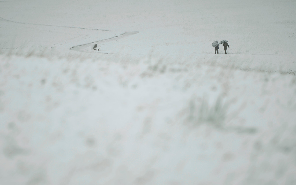 . People take a walk in Belmar Park in Lakewood, May 12, 2014. A slow moving spring snow storm has blanketed the Denver area in new snow. (Photo by RJ Sangosti/The Denver Post)