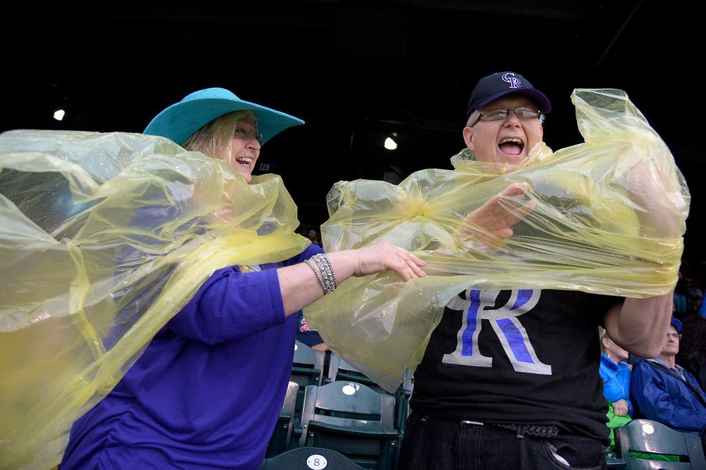 . Ann Benefield helps her husband Donnie Benefield with his ran poncho during the Colorado Rockies San Francisco May 22, 2014 at Coors Field. (Photo by John Leyba/The Denver Post)