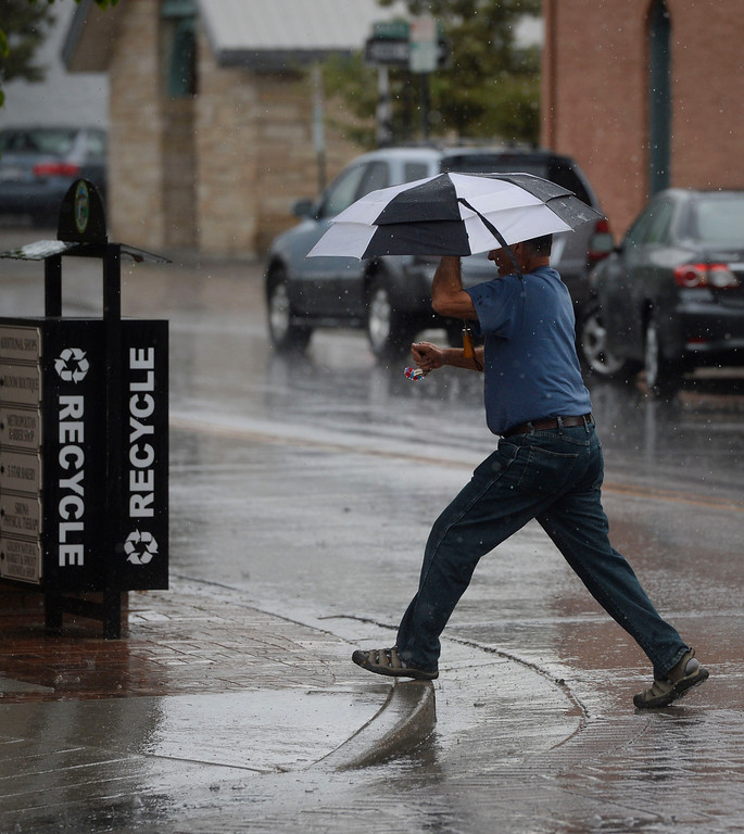 . Lou Staub, from Cincinnati, Ohio crosses 12th St. and Washington Ave in Golden, Colorado during the start of a rain storm Thursday afternoon, May 22, 2014. (Photo By Andy Cross / The Denver Post)