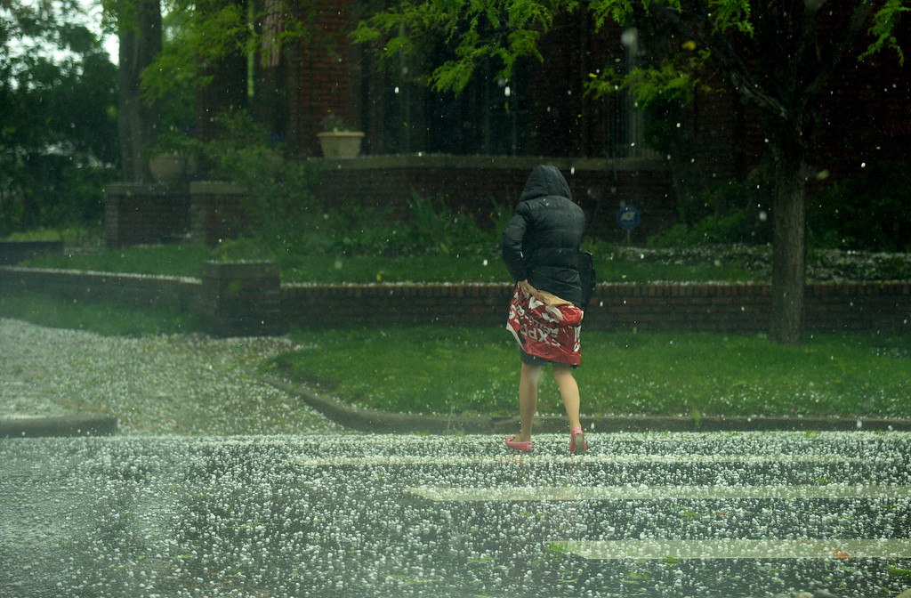 . A person across the street in the hail covering by herself with plastic bag at the corner of Grant St. and 10th ave. in Denver. Afternoon storm hit Downtown Denver. Denver, Colorado. May 22. 2014. (Photo by Hyoung Chang/The Denver Post)