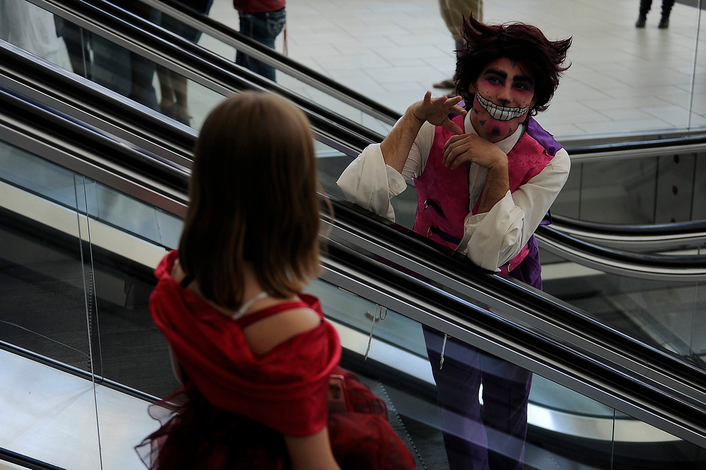 . A man dressed as a Cheshire Cat waves to people riding the escalator during Denver Comic Con at the Colorado Convention Center in Denver, Colorado on June 14, 2014. (Photo by Seth McConnell/The Denver Post)