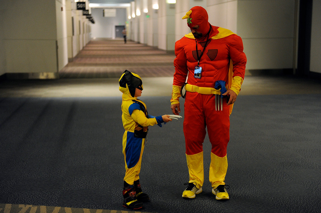 . Mike Allgire as Radio Active Man helps his son, Jack Allgire, 5, take off his Wolverine claws as they take a break during Denver Comic Con at the Colorado Convention Center in Denver, Colorado on June 14, 2014. (Photo by Seth McConnell/The Denver Post)